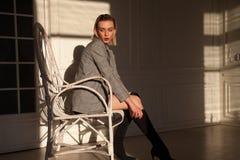 女用贴身内衣裤的时髦的女人金发碧眼的女人在一把白色扶手椅子坐在屋子里 免版税库存照片