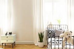 女用连杉衬裤涉及在白色卧室内部的儿童的床与在墙壁上的植物和拷贝空间 实际照片 免版税库存照片
