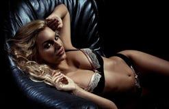 女用贴身内衣裤的妇女在皮革长沙发  库存照片