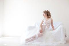 女用贴身内衣裤的美丽的女孩坐一个白色长沙发婚礼 免版税库存图片