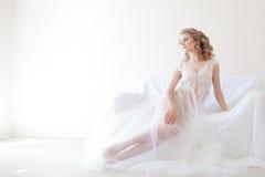 女用贴身内衣裤的美丽的女孩坐一个白色长沙发婚礼 库存照片