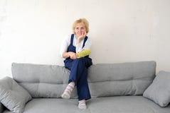 女监工有沙发的一基于在屋子里 免版税库存图片