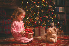 女睡袍的儿童女孩有玩具熊的在圣诞夜 库存照片