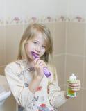 女睡袍的女孩有一把电牙刷的在卫生间里 免版税库存照片
