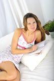 女睡袍说谎的年轻可爱和美丽的妇女在床上放松了在卧室文字日志 库存照片