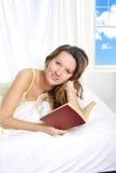 女睡袍说谎的年轻可爱的妇女在床读书小说书放松了 图库摄影