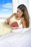 女睡袍说谎的年轻可爱的妇女在床读书小说书放松了 库存照片