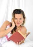 女睡袍说谎的年轻可爱的妇女在床读书小说书放松了 库存图片