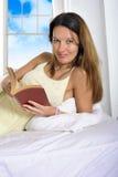 女睡袍说谎的年轻可爱的妇女在床读书放松了 库存照片