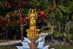 女神的金黄雕象开花的庭院佛教寺庙的在一个小泰国村庄 免版税库存照片