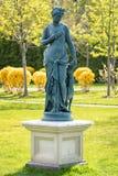 女神雕象一个古典样式的 若虫的滑稽的雕象与狗的在公园 库存照片
