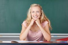 女老师用在坐在书桌的奇恩角的手 库存照片