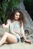 女衬衫的美丽的妇女坐沙子在灰色岩石旁边 免版税库存照片
