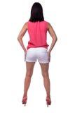 女衬衫的美丽,可爱的少妇和与一个典雅的图的短的短裤,屁股,驴子,向后站立 免版税库存照片