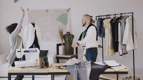女装设计师 舞蹈和衣裳的两位设计师乐趣工作在剪裁的一个创造性的演播室 时装设计师 影视素材