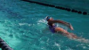 女运动员严谨地在以后的游泳竞争的自由式训练 股票录像