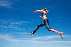 女运动员在空气保持,当跳时 库存照片