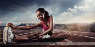 年轻女运动员舒展 免版税库存照片