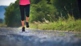女运动员赛跑者 在鞋子的特写镜头 妇女健身日落凹凸部 库存图片