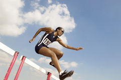 女运动员跳跃的障碍 免版税库存图片