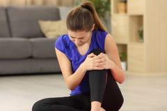女运动员遭受的膝盖疼痛在家 免版税库存图片