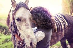女骑士拥抱他的充满喜爱的马 库存照片