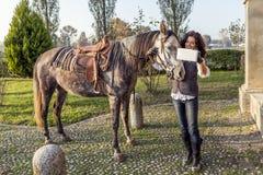 女骑士采取与他的马的一selfie 免版税库存图片