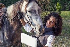 女骑士采取与他的马的一selfie 免版税库存照片