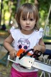 女婴举行和与一把电锯,锯一起使用 免版税库存照片