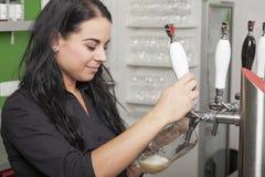 女主人轻拍新鲜的桶装啤酒 库存图片