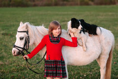 女婴年轻人 红色礼服 在马背上狗 小的白马小马 库存图片