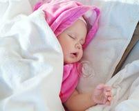女婴休眠在桃红色和空白毛巾之下 免版税库存照片