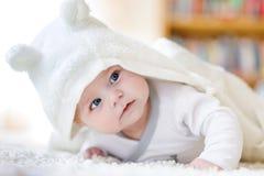 女婴佩带的白色毛巾或冬天overal在白色晴朗的卧室 免版税库存照片