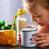 女婴倾斜了在杯子用牛奶 曲奇饼和瓶机智 免版税图库摄影