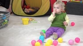 女婴吃曲奇饼和戏剧与五颜六色的继续比赛室 股票录像