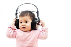 女婴听与耳机的音乐用手 免版税库存图片