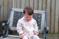 女婴哭泣的坐一把椅子在庭院里 免版税库存图片