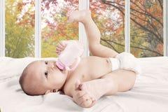 女婴喝牛奶瓶 免版税库存图片