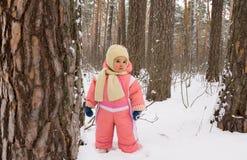 女婴在冬天森林里 免版税库存照片