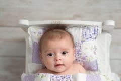 女婴在微小的床上 库存照片