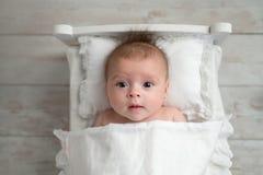 女婴在微小的床上 免版税库存图片