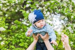 女婴在春天开花的庭院里 免版税库存图片