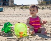 女婴在海滩的品尝沙子 库存照片