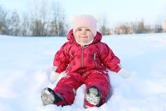 女婴在温暖的衣裳的11个月坐雪室外在wint 免版税库存照片