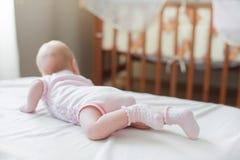 女婴在白色床上爬行 免版税库存图片