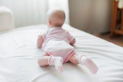女婴在白色床上爬行 库存图片