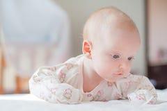 女婴在白色床上爬行 免版税图库摄影