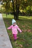 女婴在美丽的公园在秋天 免版税库存照片