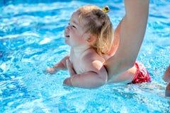 女婴在水池学会游泳 免版税图库摄影