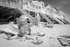 女婴在te沙子坐笑的海滩使用和 免版税图库摄影
